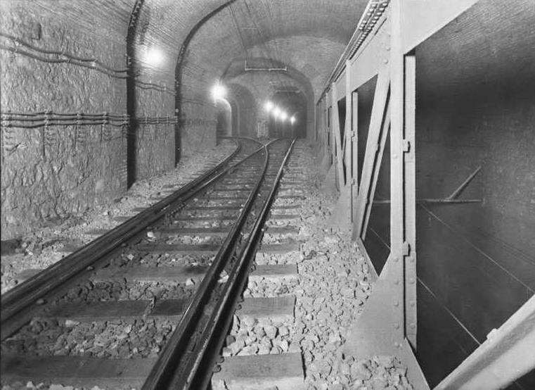 """Sala de la bifurcación desde la junta de contra aguja del desvío talonable de la vía 2 (ascendente), y excelente vista de la viga tipo Pratt. A la derecha, el nivel inferior correspondiente a la vía 1 (descendente). Al fondo el emboquillado de los túneles para vía sencilla, el de la derecha hacia la estación """"Cataluña"""", el de la izquierda hacia la estación """"Urquinaona"""". Fuente: Archivo Brangulí."""